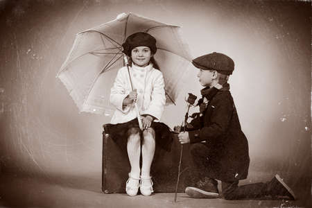 lovely: Cute little boy is giving a rose to the charming little lady. Retro style. Stock Photo