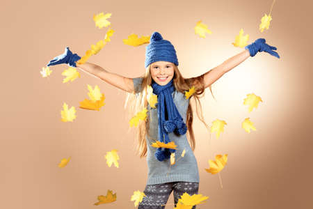 Joyful cute girl in autumn clothes throwing maple leaves. Stock Photo - 17383449
