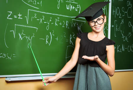 young schoolgirl: Portrait of a cute schoolgirl in academic hat and big round spectacles at a classroom.