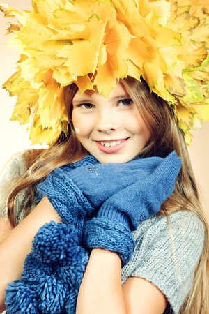 Portrait of a smiling girl in autumn clothes and a hat of maple leaves. photo