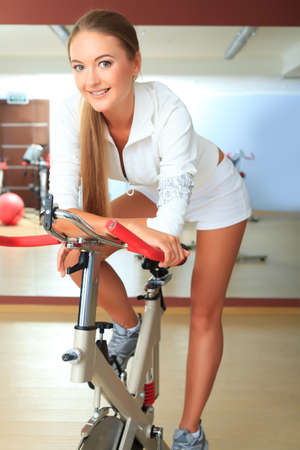 Young sporty woman doing exercise on bicycle in the gym centre. photo