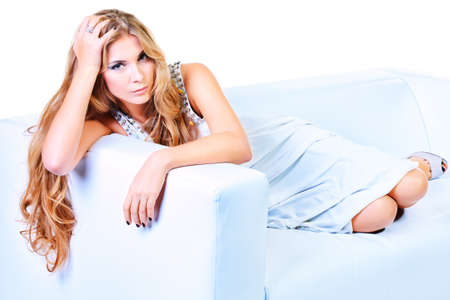 woman long hair: Beautiful young woman with magnificent blonde hair sitting on a sofa. Isolated over white.