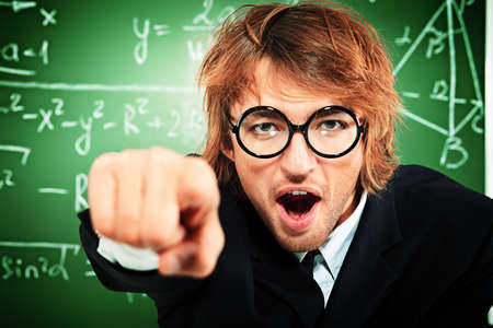 Portrait of the angry male tutor near the blackboard. Stock Photo - 17417956