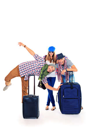 arriving: Group of cheerful young people standing together with suitcases over white background.