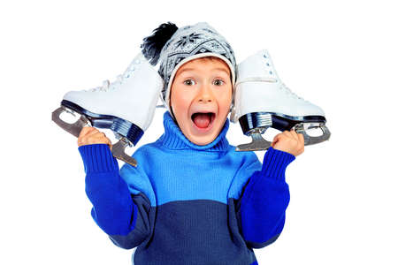 Cheerful little boy in warm sweater and hat  holding figure skates. Isolated over white background Stock Photo