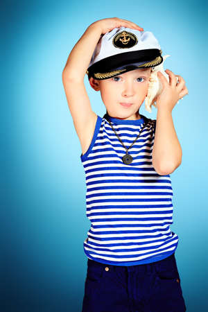 Little smiling sailor boy is listening to the sound of the sea in the shell. Stock Photo - 17444962