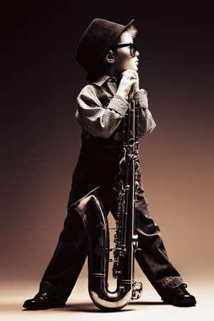 saxofón: Retrato de un niño pequeño lindo músico de jazz tocando su saxofón. Estilo retro.