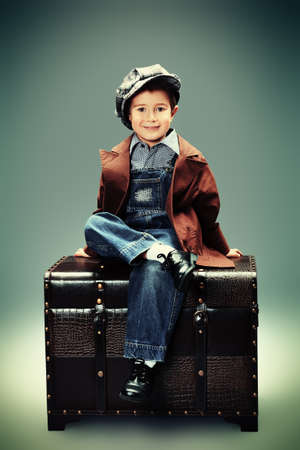 fashion boy: Portrait of a cute little boy sitting with a huge old trunk. Vintage style.