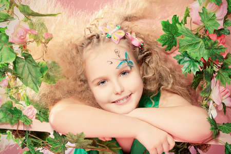 Beautiful little fairy among the thickets of ivy over pink background. photo