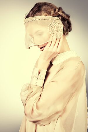Charming fashionable model in elegant light dress posing at studio. Stock Photo - 17496045