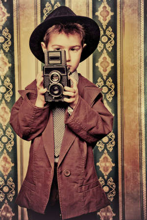 retro styled: Little boy looking like a gentleman standing with a camera. Vintage background.