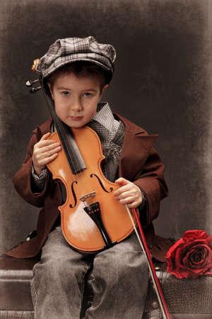 violist: Portret van een kleine jongen zittend op een grote oude koffer met zijn viool. Retro stijl.