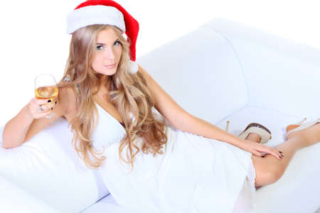 Beautiful blonde woman in festive white dress and christmas hat sitting on a sofa. Isolated over white. photo