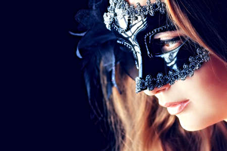 female mask: Portrait of a beautiful young woman in a carnival mask. Over black background.