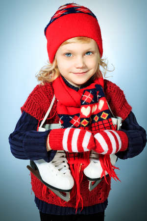 Portrait of a cute little girl in warm hat and sweater posing with figure skates. photo