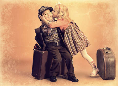vintage children: Charming little girl is kissing cute little boy sitting on the old suitcase. Retro style. Stock Photo