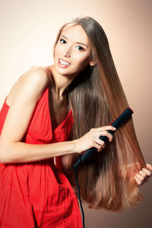 Beautiful young woman doing hairstyle with hair iron.