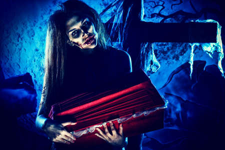 terrific: Bloodthirsty witch standing at the night cemetery and holding a coffin. Stock Photo