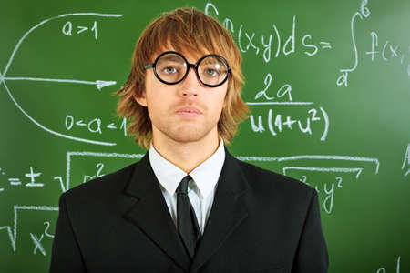 Portrait of a smart male student in a suit standing near the blackboard. Stock Photo - 17698960