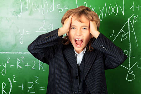 Schoolboy holding his head and shouting at a classroom. photo