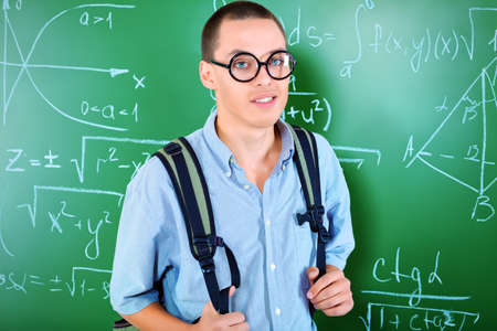 Young man student standing at the blackboard in the classroom. Stock Photo - 17698964