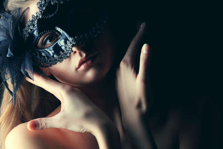 antifaz de carnaval: Retrato de una joven y bella mujer con una máscara de carnaval. Sobre fondo negro. Foto de archivo