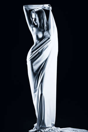 erotic girl: Art portrait of a beautiful naked woman, wrapped in elastic fabric. Black background. Stock Photo