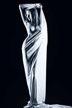 erotico: Ritratto di arte di una bella donna nuda, avvolta in tessuto elastico. Sfondo nero.