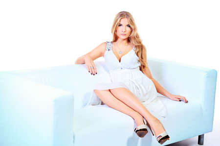Beautiful young woman with magnificent blonde hair sitting on a sofa. Isolated over white. Stock Photo - 17861203