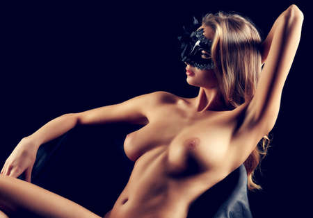 nude lady: Portrait of a beautiful naked woman in carnival mask posing over black background. Stock Photo