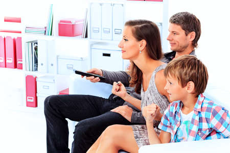 family sofa: Happy family emotionally watching television at home. Stock Photo