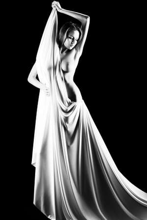 Art portrait of a beautiful naked woman, wrapped in elastic fabric. Black background. Stock Photo