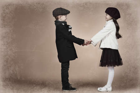 Cute little boy holding hands with a girl. Retro style. photo