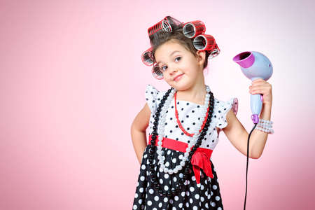 kids dress: Portrait of a cute little pin-up girl over pink background.