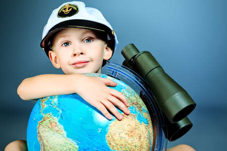 Little sailor boy sitting with the globe and binoculars. Stock Photo - 17800204