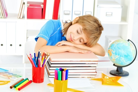 Tired boy is sleeping on his books. Education. photo