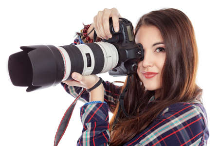 Pretty young woman taking pictures on the camera. Isolated over white.