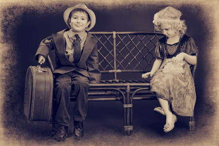 gentlemen: Cute little boy with an old suitcase is sitting on a bench with charming little lady. Retro style.