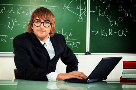 Portrait of a smart male student in a suit working on a laptop at a classroom.  Stock Photo - 17923199