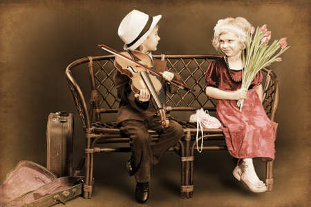 Cute little boy is playing the violin to the charming little lady. Retro style. photo