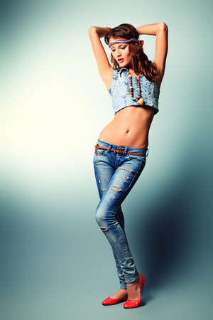 Full length portrait of an attractive young woman in jeans clothing.