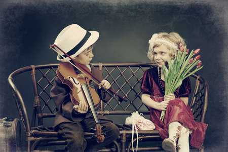 woman violin: Cute little boy is playing the violin to the charming little lady. Retro style. Stock Photo