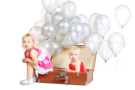 Two little girls are sitting in the old suitcase under many balloons. Isolated over white. photo