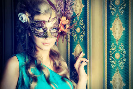 female mask: Portrait of a beautiful young woman in a carnival mask. Vintage style. Stock Photo