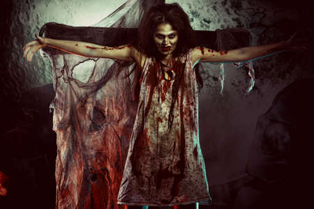 Bloodthirsty zombi standing at the night cemetery in the mist and moonlight.