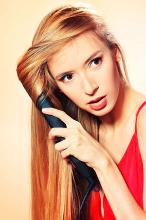 Beautiful young woman doing hairstyle with hair iron. photo
