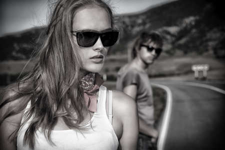 fashionable sunglasses: Couple of modern young people posing on a road over picturesque landscape.