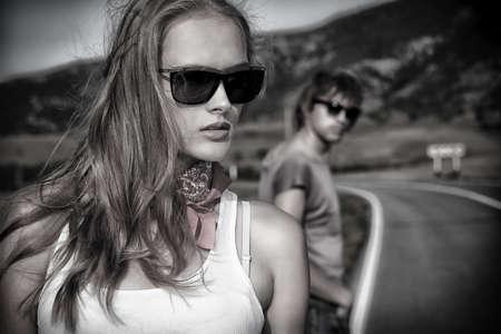 sunglasses: Pareja de j�venes modernos que presenta en una carretera sobre el paisaje pintoresco.