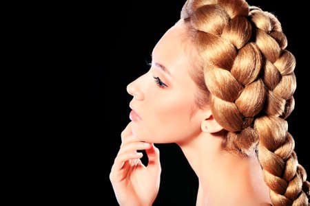 Beautiful blonde woman with fashionable hairstyle. Over black background. photo