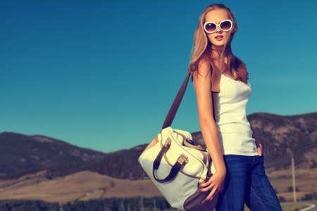 Mooie jonge vrouw die op een weg in het schilderachtige landschap.